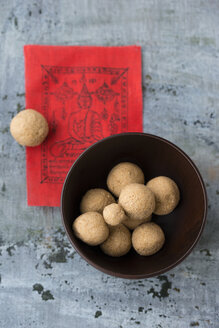 Bowl of Tsampa balls and  red prayer flag on grey ground - MYF000729