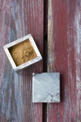 Little box of cinnamon powder on wood - MYF000739