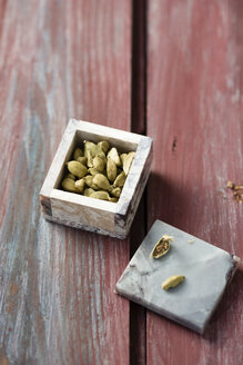 Little box of cardamom capsules on wood - MYF000743