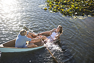 Playful young couple in a rowing boat on a lake - ZEF002333