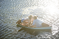 Young couple kissing in a rowing boat on a lake - ZEF002335