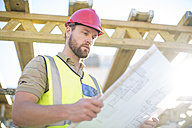 Construction worker reading plan at construction site - ZEF001655
