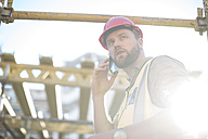 Construction worker on cell phone on construction site - ZEF001658