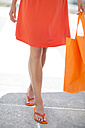 Orange dressed woman with shopping bag and flip-flops - ZEF002107