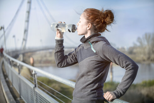 Young woman drinking water out of a bottle after jogging - SEGF000070