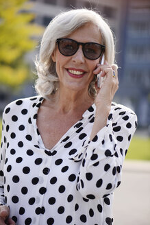 Portrait of smiling senior woman wearing sunglasses telephoning with smartphone - VRF000129
