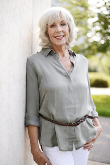 Portrait of smiling white haired senior woman leaning against concrete wall - VRF000120