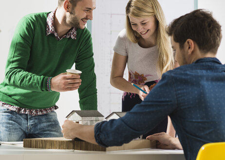 Three smiling young architects in office discussing - UUF002804