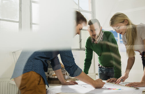 Three young architects in office discussing - UUF002811