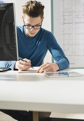Young man at desk writing - UUF002841