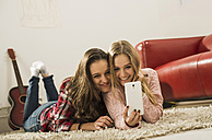 Two female friends taking a selfie with smartphone at home - UUF002744