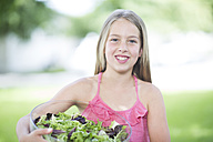 Portrait of a smiling girl holding a bowl of salad - ZEF002755