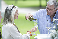 Senior man pouring wine for his wife outdoors - ZEF003464