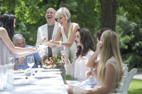Woman dishing up salad on a garden party - ZEF003467