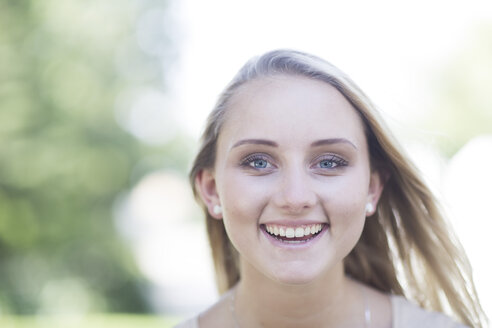 Portrait of smiling blond young woman outdoors - ZEF003498