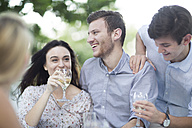Happy friends drinking wine outdoors - ZEF003503