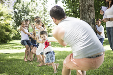 Kids and young man competing in tug of war - ZEF002823