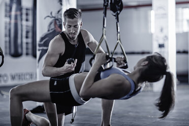 Fitness trainer keeping time with woman doing pull-ups - ZEF002618