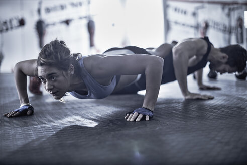 Man and woman doing push-ups in gym - ZEF002622