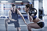 Trainer watching woman doing fitness training with weights - ZEF002627