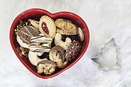 Heart-shaped bowl of different Christmas Cookies and a cookie cutter on an angel wing - SARF001143