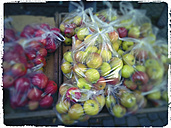 Apples in plastic bags at market stall - MYF000757