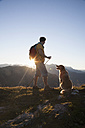 Austria, Tyrol, Unterberghorn, hiker with dog at sunrise - RBF002100