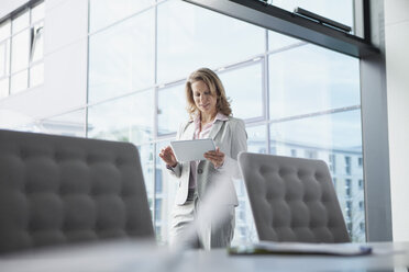 Businesswoman in conference room using digital tablet - RBF002101