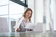 Businesswoman using laptop in conference room - RBF002113