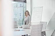 Businesswoman using laptop in conference room - RBF002118