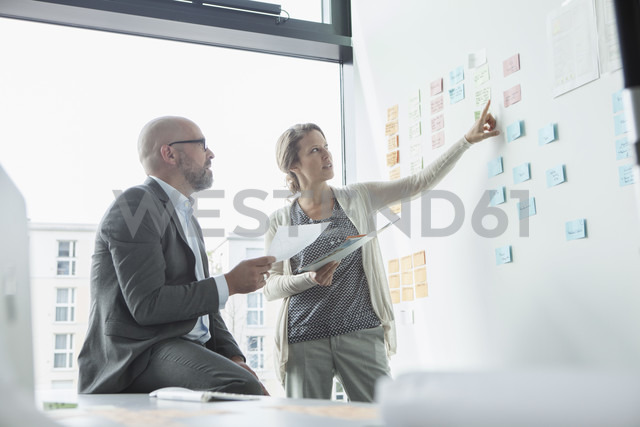 Businessman and businesswoman in office at wall with adhesive notes - RBF002135
