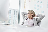 Businesswoman in office leaning back - RBF002122