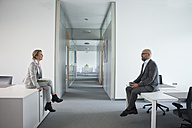 Two colleagues sitting on office floor - RBF002140