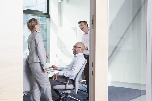 Three businesspeople in conference room - RBF002152