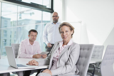 Three businesspeople with laptop in conference room - RBF002159