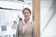 Portrait of smiling businesswoman in office - RBF002165