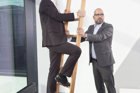 Businessman holding career ladder for colleague - RBF002158