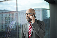 Businessman at the window on cell phone - RBF002175