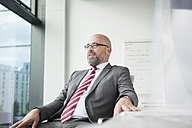 Confident businessman in office looking out of window - RBF002178