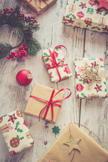 Wrapped Christmas presents and red Christmas bauble on wood - SARF001150