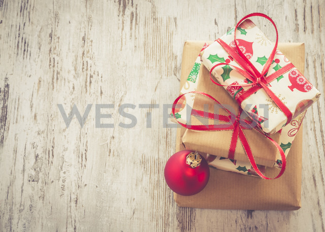 Stack of Christmas presents and red Christmas bauble on wood - SARF001151
