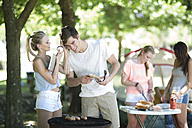 Friends on holiday grilling sausages and listening to music on a digital tablet - ZEF003280