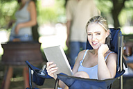 Smiling young woman sitting on a camping chair with a digital tablet - ZEF003283