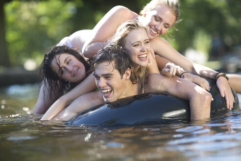 Friends on holiday having fun with inner tube in a pool - ZEF003296