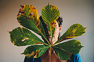 Woman with leaf in front of face - ZM000350