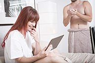 Young woman sitting on bed using digital tablet - ZEF002930
