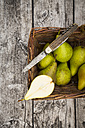 Wickerbasket with pears and pocket knife on grey wood - LVF002464