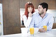 Couple in kitchen having breakfast with orange juice - ZEF002639