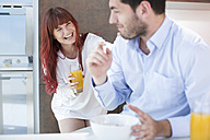 Playful couple in kitchen having breakfast - ZEF002642