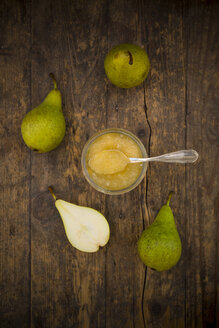 Whole and sliced organic pears and glass of pear jam on dark wood - LVF002474